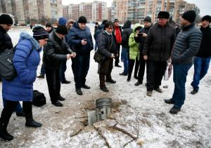 People look at remains of rocket shell on street in town of Kramatorsk
