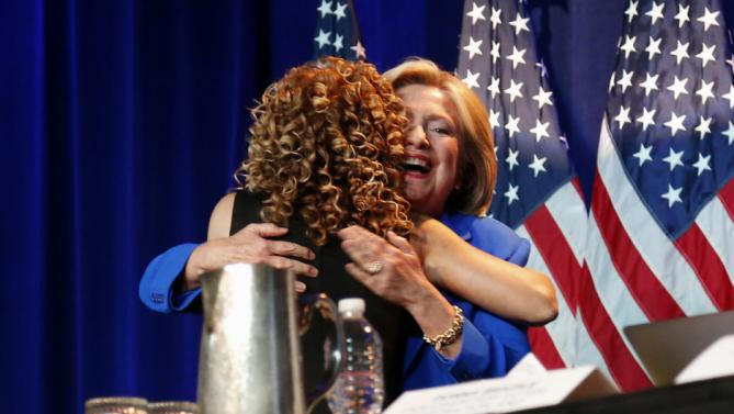 Democratic presidential candidate, Hillary Rodham Clinton, right, hugs Democratic National Committee (DNC) Chair Rep. Debbie Wasserman Schultz, D-Fla. before addressing the summer meeting of the Democratic National Committee, Friday, Aug. 28, 2015, in Minneapolis. (AP Photo/Jim Mone)