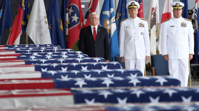 Vice President Mike Pence and Admiral Phil Davidson (C), U.S. Indo-Pacific Commander, honor the remains of U.S. soldiers from the Korean War at Joint Base Pearl Harbor in Honolulu